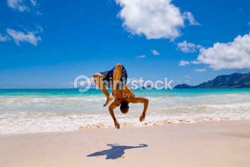d9e43a51cad3f8 Man Doing Backflip On The Beach Stock Photo