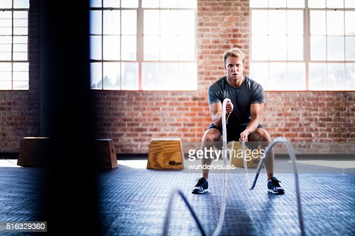 Hombre haciendo batalla cuerdas ejercicio durante entrenamiento en un gimnasio CrossFit