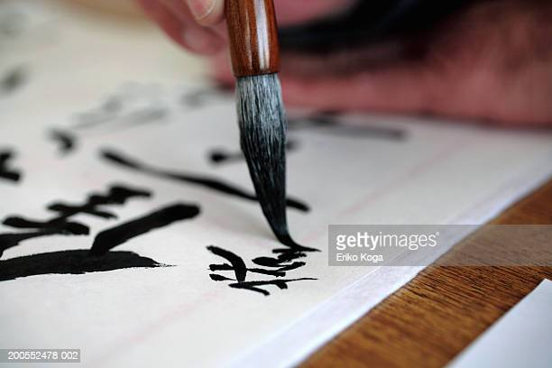Man doing calligraphy, selective focus, close-up