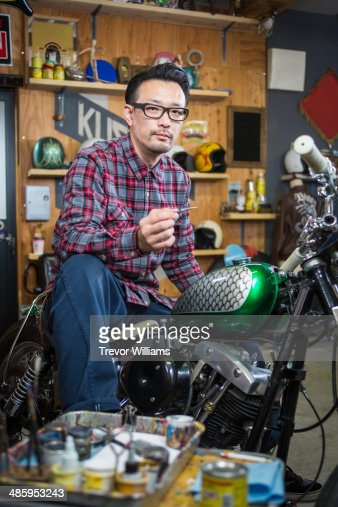 man doing custom paint on a motorcycle gas tank. Black Bedroom Furniture Sets. Home Design Ideas