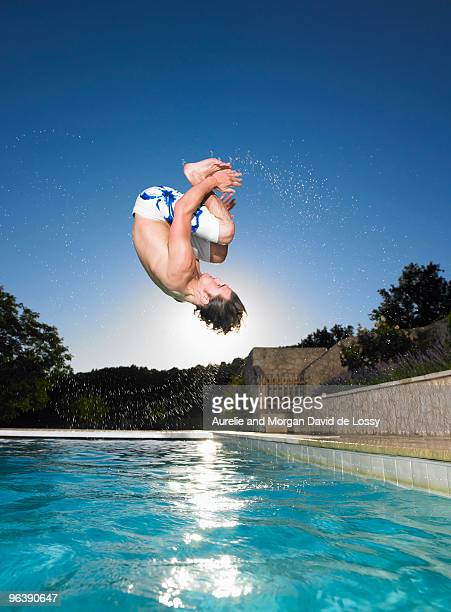 man doing flip into pool