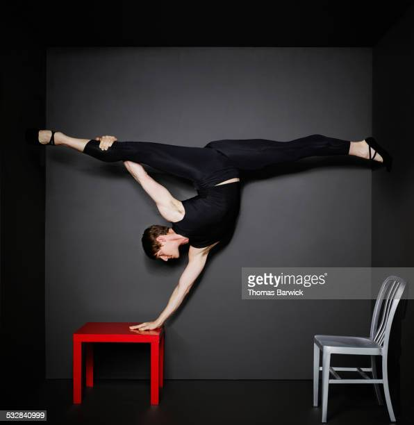 Man doing hand stand and splits on table in room