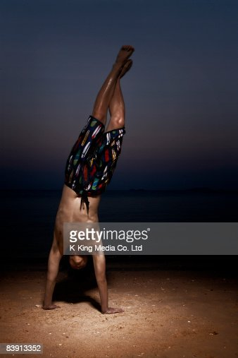 Man doing handstand on beach at dusk. : Stock Photo