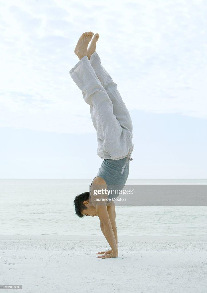 Man doing handstand on beach : Stock Photo