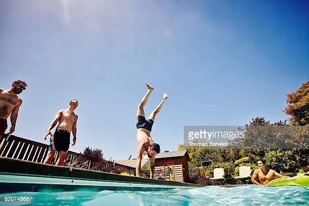 Man doing handstand on edge of pool