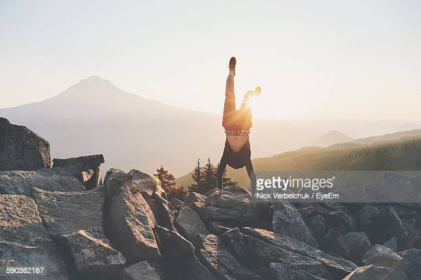 Man Doing Handstand On Rocks Against Sky During Sunrise