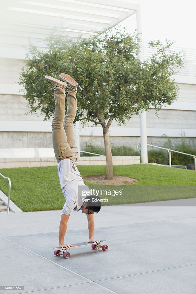 Man doing handstand on skateboard : Stock Photo
