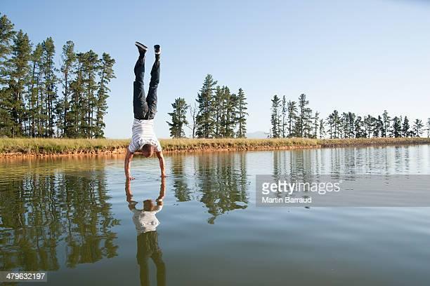 Mann macht handstand am Wasser