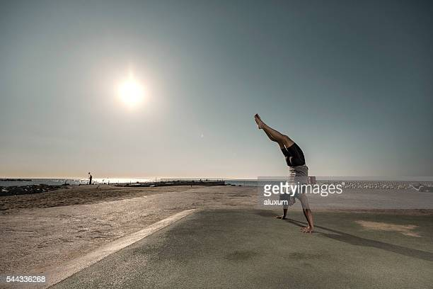 Man doing headstand at sunrise