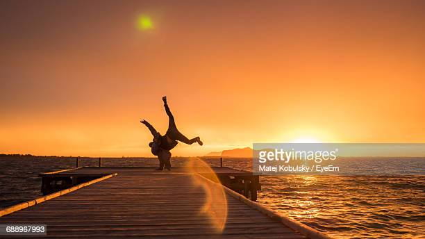 Man Doing Headstand On Pier Over Sea Against Clear Sky During Sunset