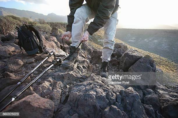 Man doing his shoes during trekking in mountains