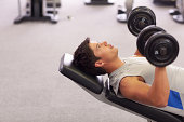 Man doing incline chest presses with dumbbells in gymnasium