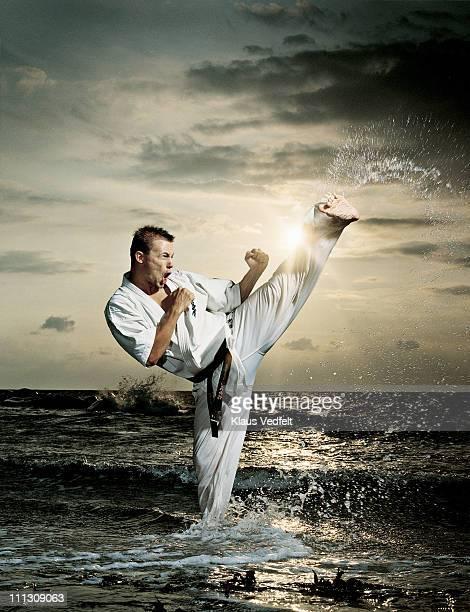 Man doing karate kick in the ocean