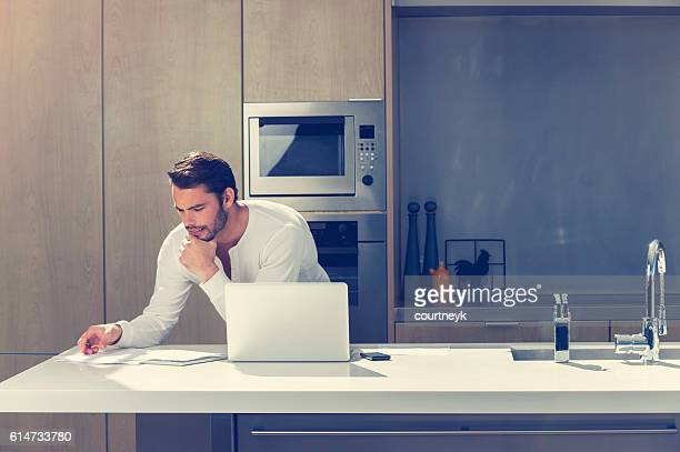 Man doing paperwork with a laptop