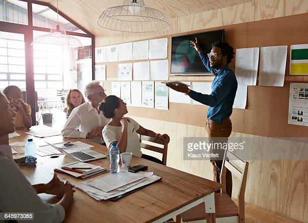 Man doing presentation, using tablet & screen