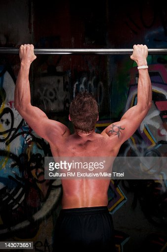 Man doing pull-ups in graffitied gym : Foto de stock