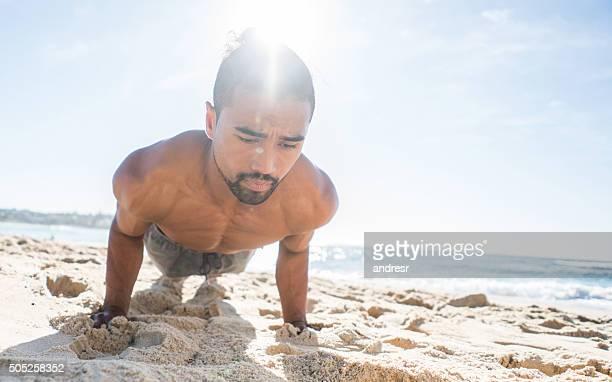 Homme faisant push ups à la plage