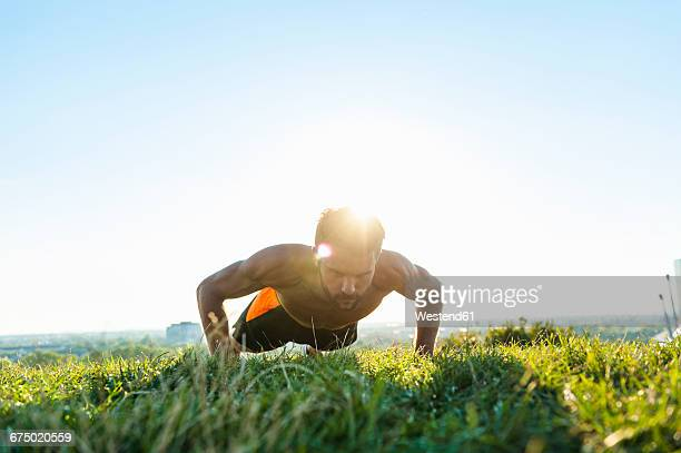 Man doing pushups on a meadow