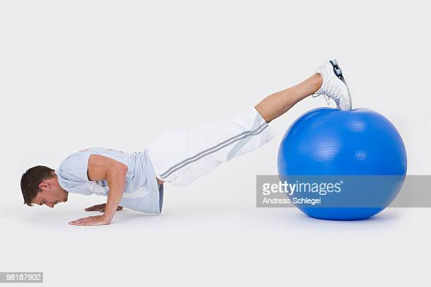 A man doing push-ups with an exercise ball