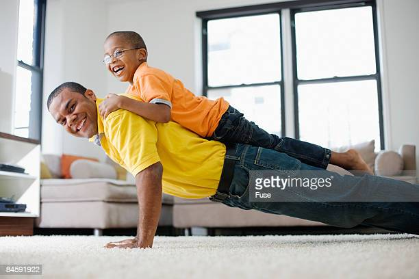 Man Doing Pushups with Son on His Back