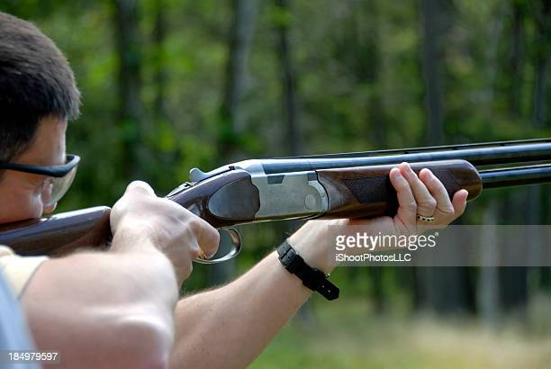 Man doing skeet shooting in the middle of a forest