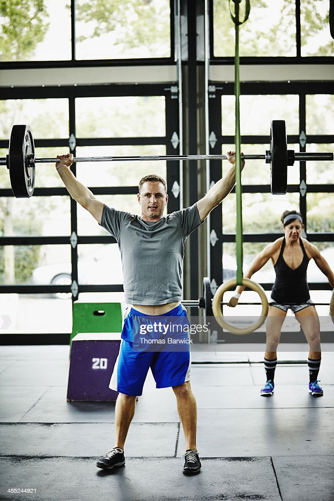 Man doing snatch with barbell in Gym gym