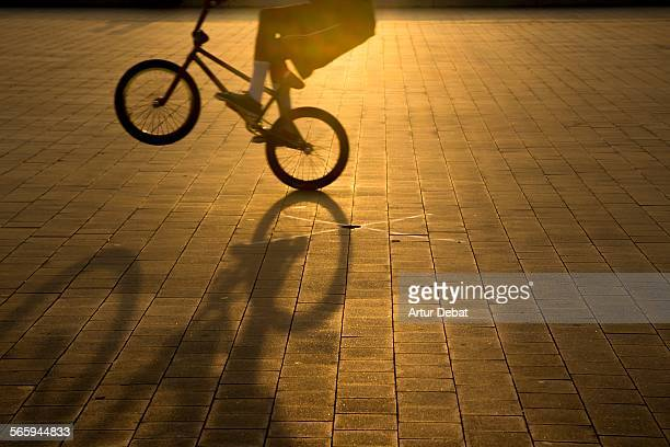 Man doing tricks with bike with shadow on sunset