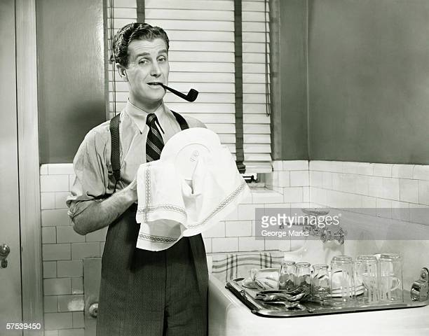 Man doing washing dishes in kitchen, pipe in teeth, (B&W)