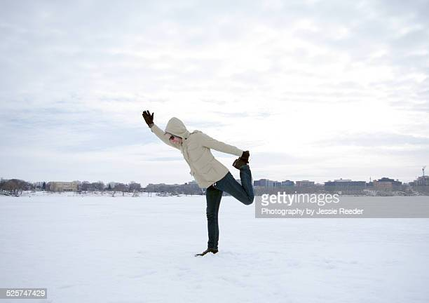 Man doing yoga on frozen lake in snow