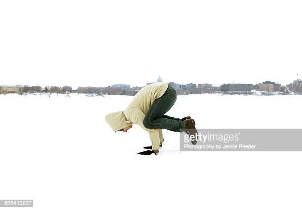 Man doing yoga pose outside in snow