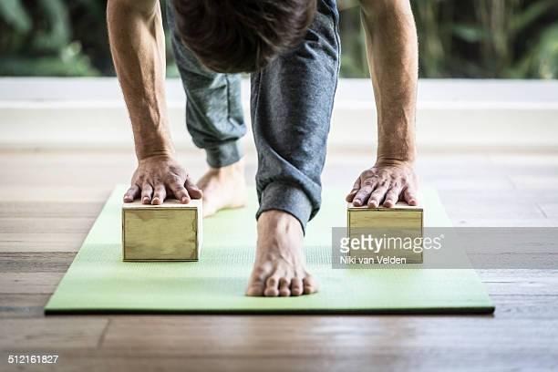 Man doing yoga with blocks in yoga studio