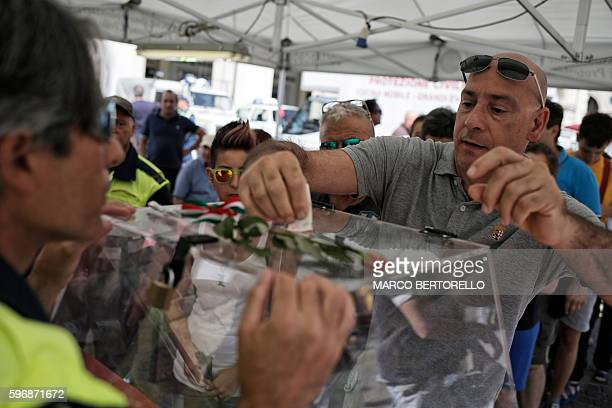 A man donates money during a charity event in Piazza San Carlo in Turin on August 28 whose profits are to help the population hit by the quake in...