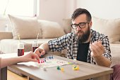 Couple in love playing ludo board game and having fun. Guy throwing dices and making a new move