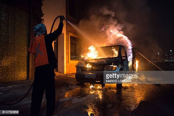 A man douses a van on fire in front of the popular jazz bar 'the Orbit' in the Braamfontein district of Johannesburg on October 14 2016 during riots...