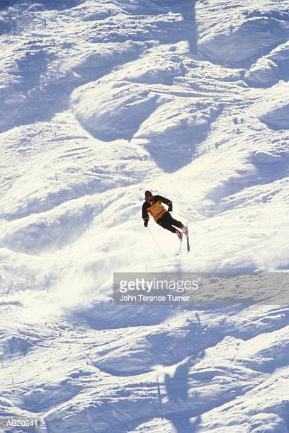 Man downhill skiing over Moguls