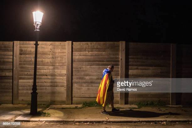 A man draped in a Catalan independence flag checks his phone during a protest against the judge order on Catalan leaders to be held in custody in...
