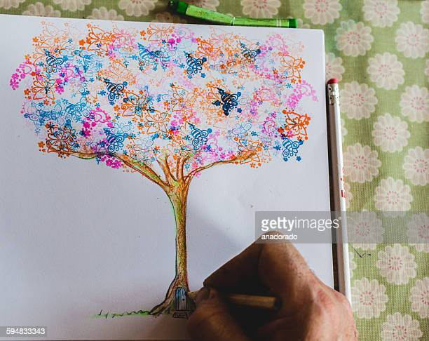 Man drawing an illustration of a magical tree
