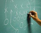 Man drawing football play diagram on blackboard, close-up