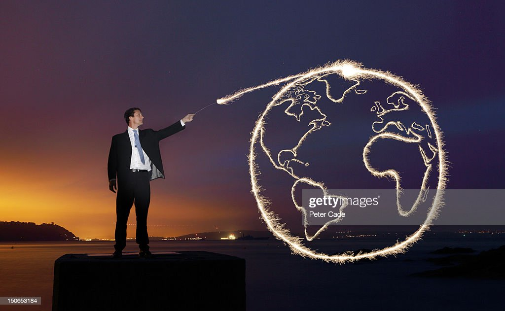 Man drawing the earth with a sparkler : Stock Photo