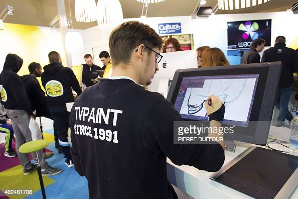 A man draws onto a graphic tablet as visitors attend the Angouleme International Comics Festival on January 29 2015 in Angouleme The world's leading...