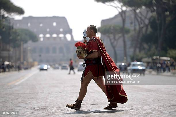 A man dressed as a ancient Roman centurion walks by the Colosseum in the center of Rome on April 15 2015 FILIPPO MONTEFORTE/AFP PHOTO / AFP / FILIPPO...