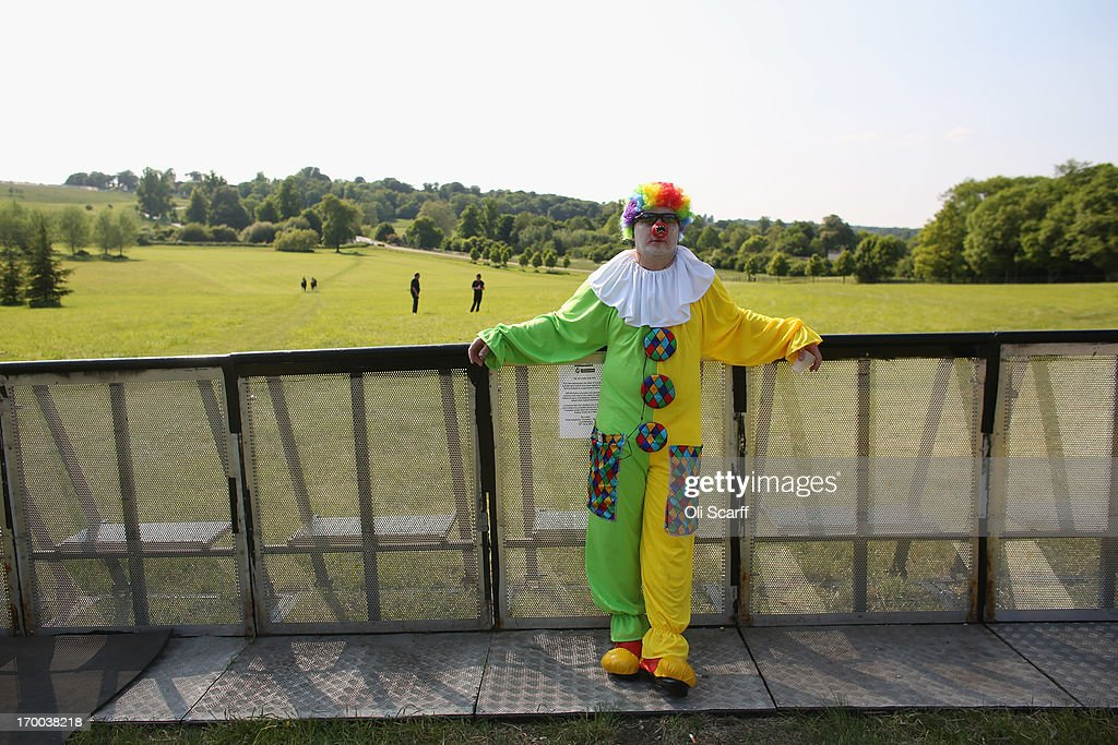 A man dressed as a clown stands in the protester encampment outside The Grove hotel, which is hosting the annual Bilderberg conference, on June 6, 2013 in Watford, England. The traditionally secretive conference, which has taken place since 1954, is expected to be attended by politicians, bank bosses, billionaires, chief executives and European royalty.