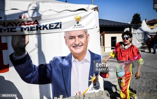 A man dressed as a clown walks past an 'EVET' campaign billboard showing the portrait of Turkish prime minister Binali Yildirim on March 29 2017 in...