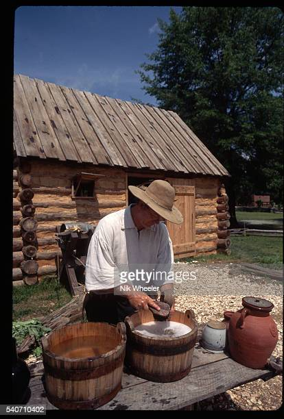A man dressed as a farmer in the 1780s washes dishes in a bucket of water Yorktown Victory Center Virginia
