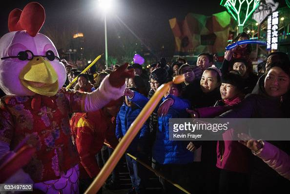 A man dressed as a 'Fire Rooster' gives out balloons to the crowd at a fair at a local park on the fifth day of the Chinese Lunar New Year on...