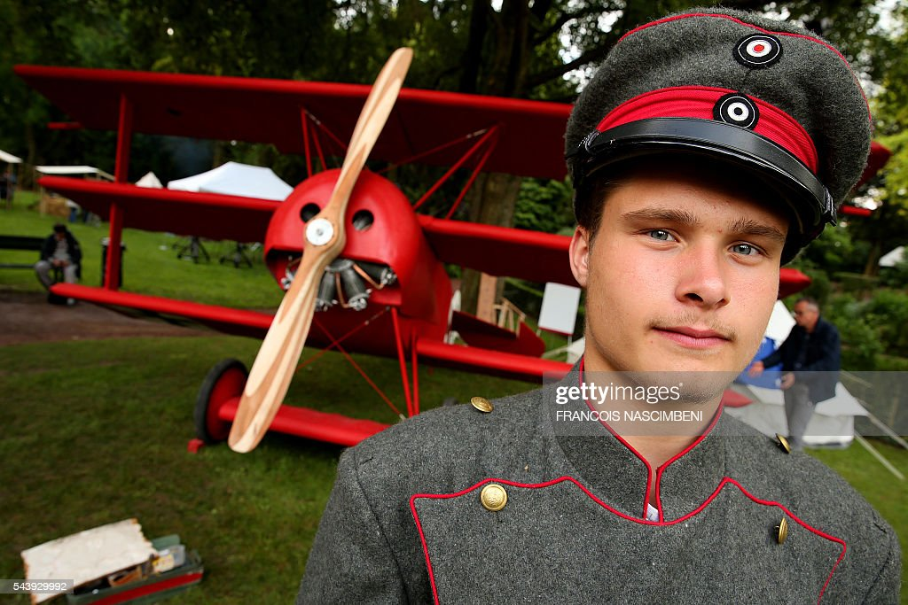 A man dressed as a German WWI pilot stands in front of a replica of the Fokker Dr.I, the fighter aircraft of German Manfred von Richthofen aka the Red Baron during a ceremony to commemorate the centenary of the battle of the Somme, one of the deadliest of the World War I (1.2 million killed, missing and wounded in five months), on June 30, 2016 in Albert, northern France. / AFP / FRANCOIS