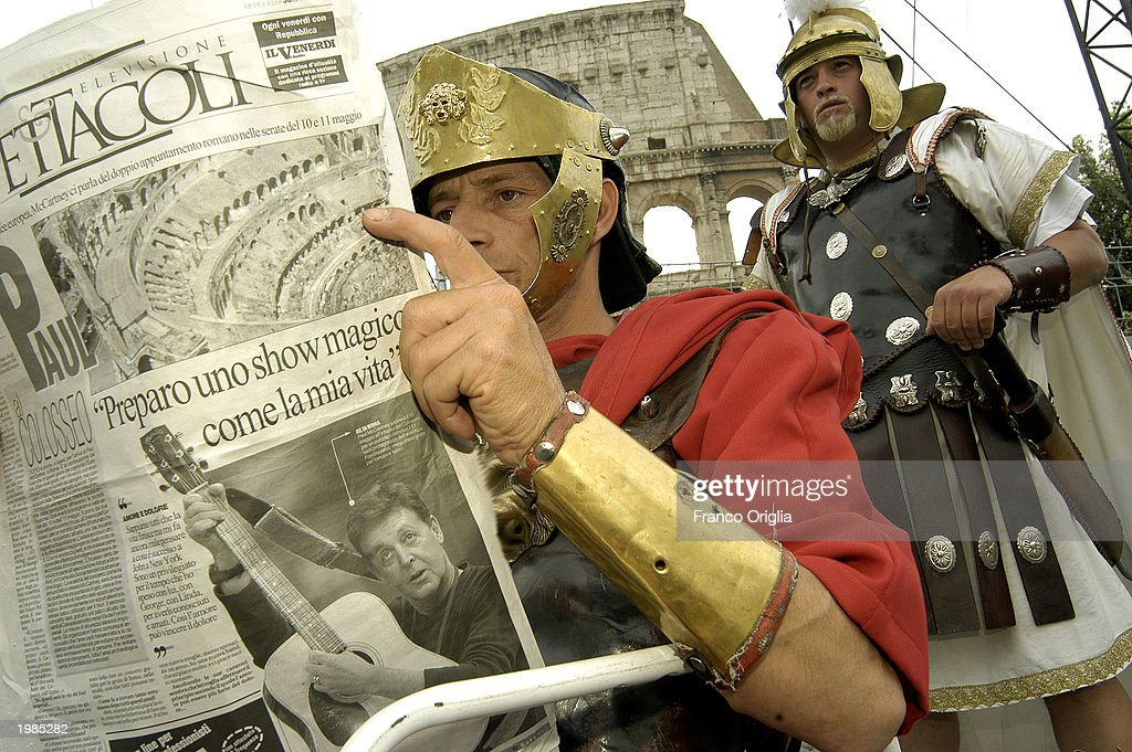 A man dressed as a gladiator reads about Paul McCartney's concert at the Colosseum May 9 2003 in Rome Italy McCartney will give a benefit concert...