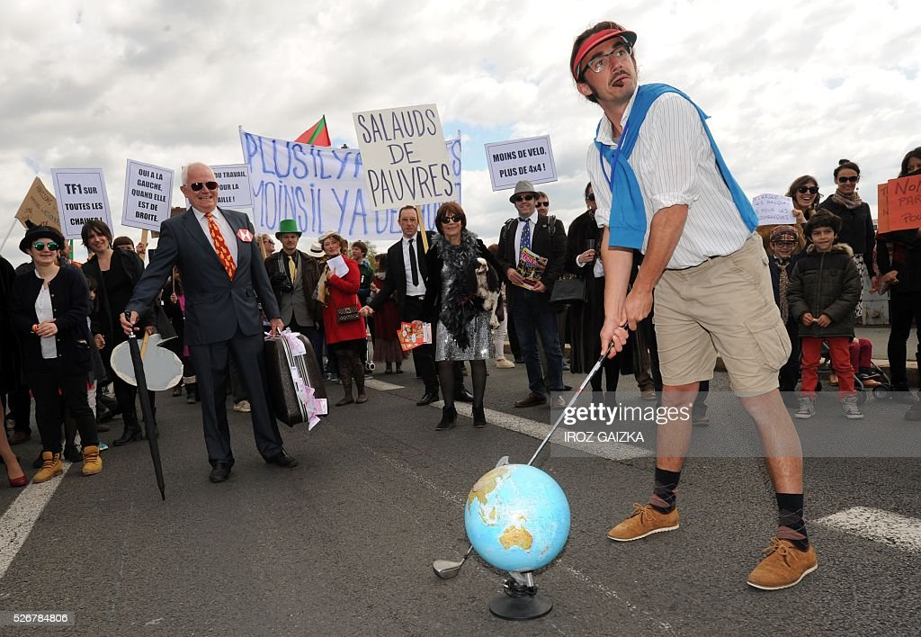 A man dressed as a golfer aims his club at a globe as members of the movement 'Bizi !' ('live' in Basque) stage a 'Rich peoples protest' to mark May Day in Bayonne on May 1, 2016. / AFP / IROZ