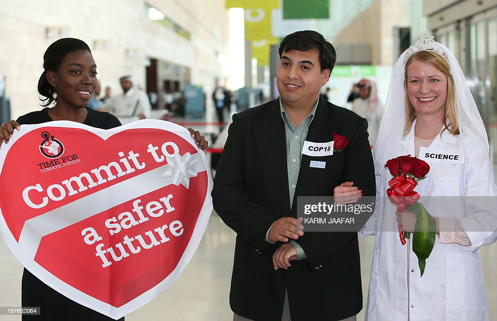 A man dressed as a groom (C) and representing the 'COP18', the 18th 'Conference of the Parties' which represents all the countries taking part in the United Nations Framework Convention on Climate Change (UNFCCC), and a woman dressed as a bride (R), representing 'science', perform a mock wedding ceremony on the sidelines of the UN Climate conference in the Qatari capital Doha on December 5, 2012. The European Union and United States said they would not make concrete near-term funding pledges at UN climate talks to help developing countries cope with the fallout from global warming. AFP PHOTO / AL-WATAN DOHA / KARIM JAAFAR == QATAR OUT ==