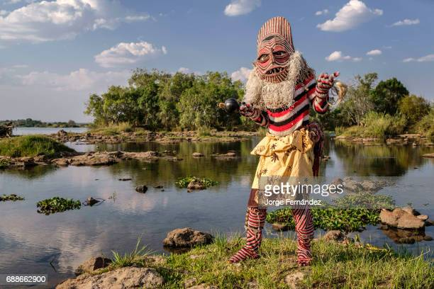 FALLS MATABELELAND ZIMBABWE Man dressed as a Makishi posing to the camera by the Zambezi river bank The Makishi is a character that for the...